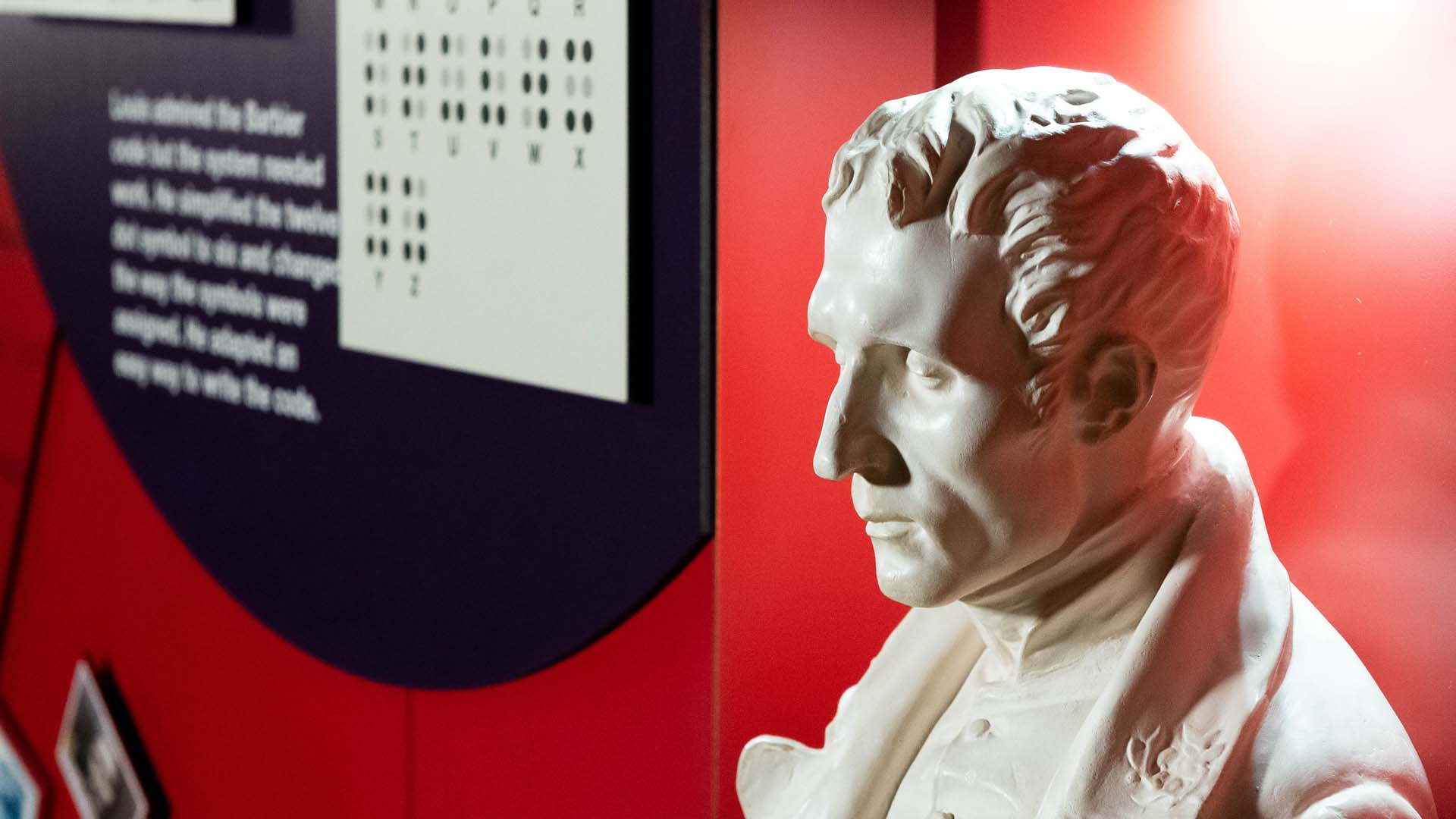 A white plaster bust of Louis Braille beside a museum exhibit wall explaining the braille system