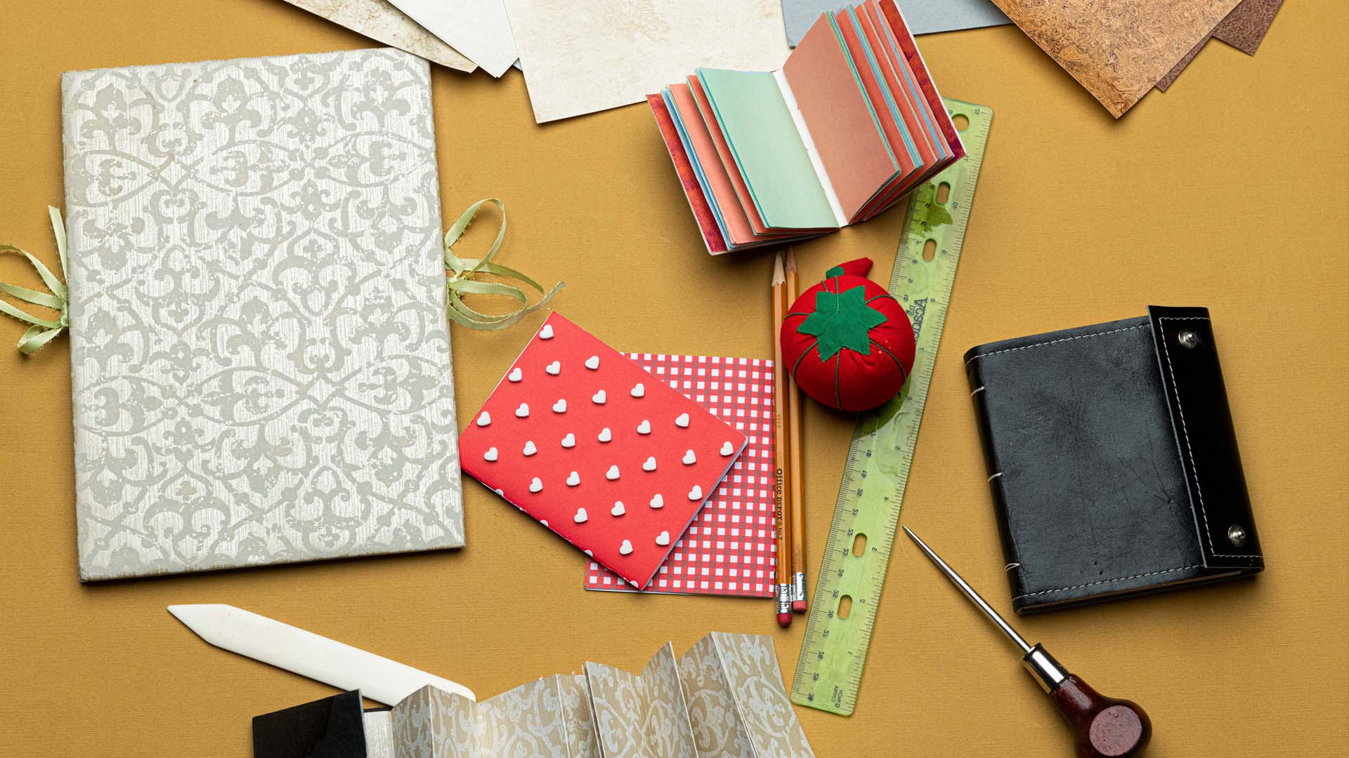 Tools and materials for a bookmaking activity, including colorful paper, a ruler, an awl, pencils, a bone burnishing tool, and finished handmade booklets