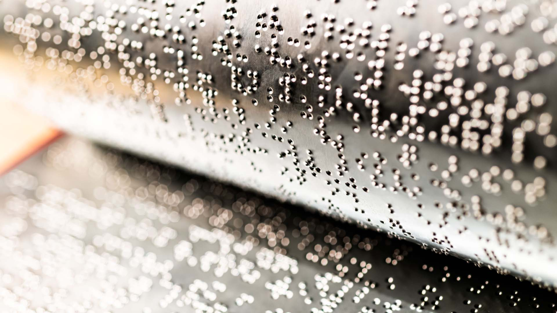 Closeup view of metal embossing plates covered with braille symbols