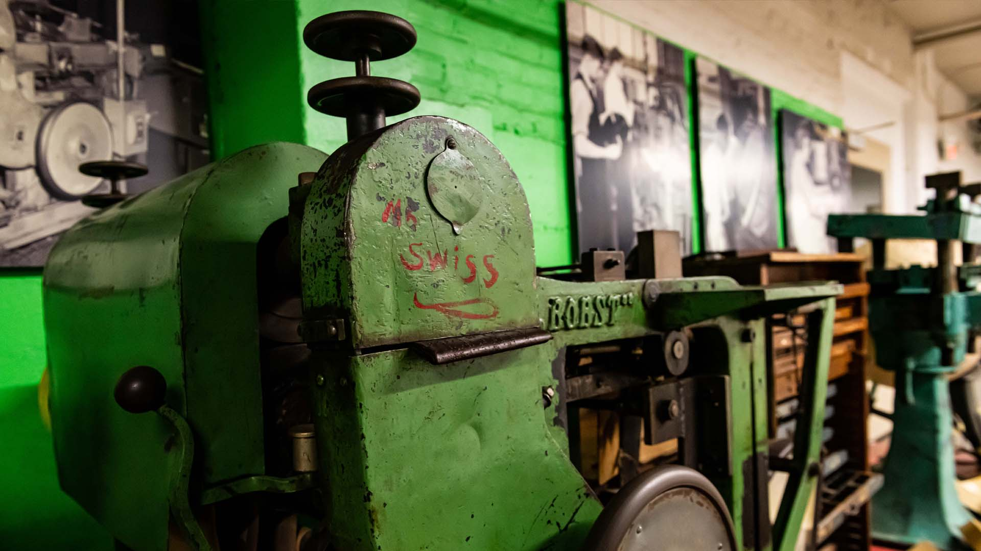 """Closeup of green metal casing on a printing press in a museum exhibit. Cast into the frame at right is """"Bobst."""" Painted onto the casing in red is """"Mr. Swiss."""""""