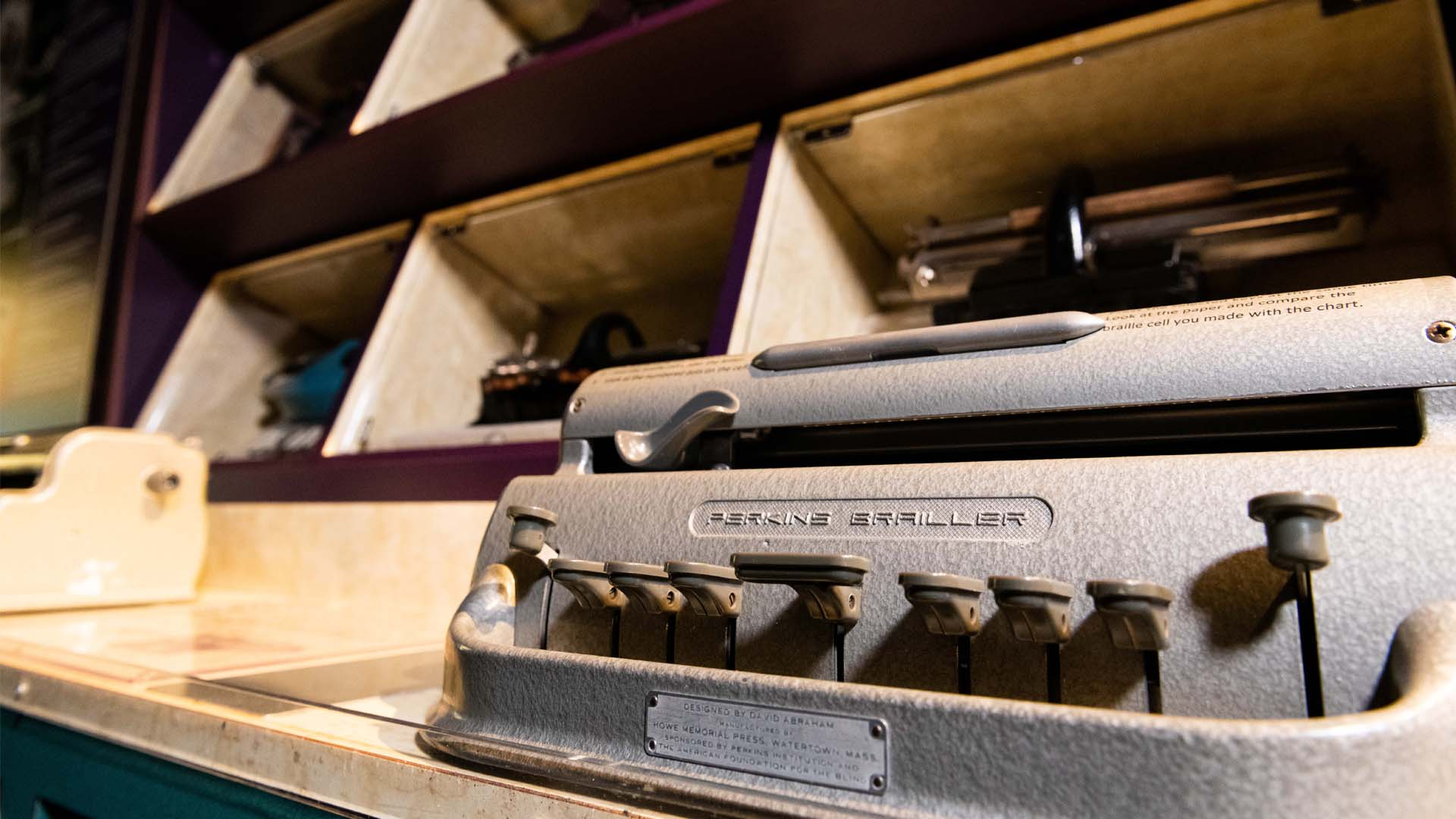 Closeup view of the keyboard of a Perkins Brailler in front of a case full of other historic braillewriters