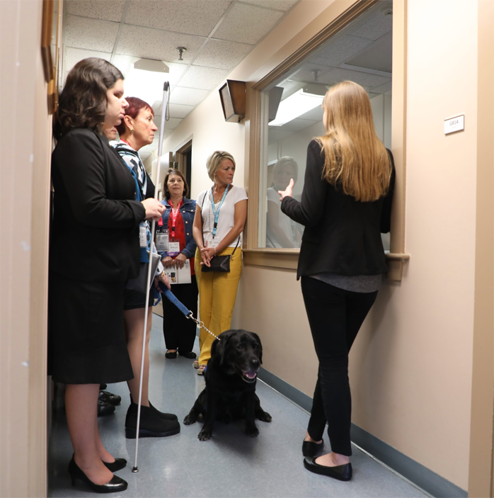 People, some carrying long canes or using guide dogs, stand in a narrow corridor looking through a large glass window. A young woman with long hair gestures as she explains what is going on behind the window.