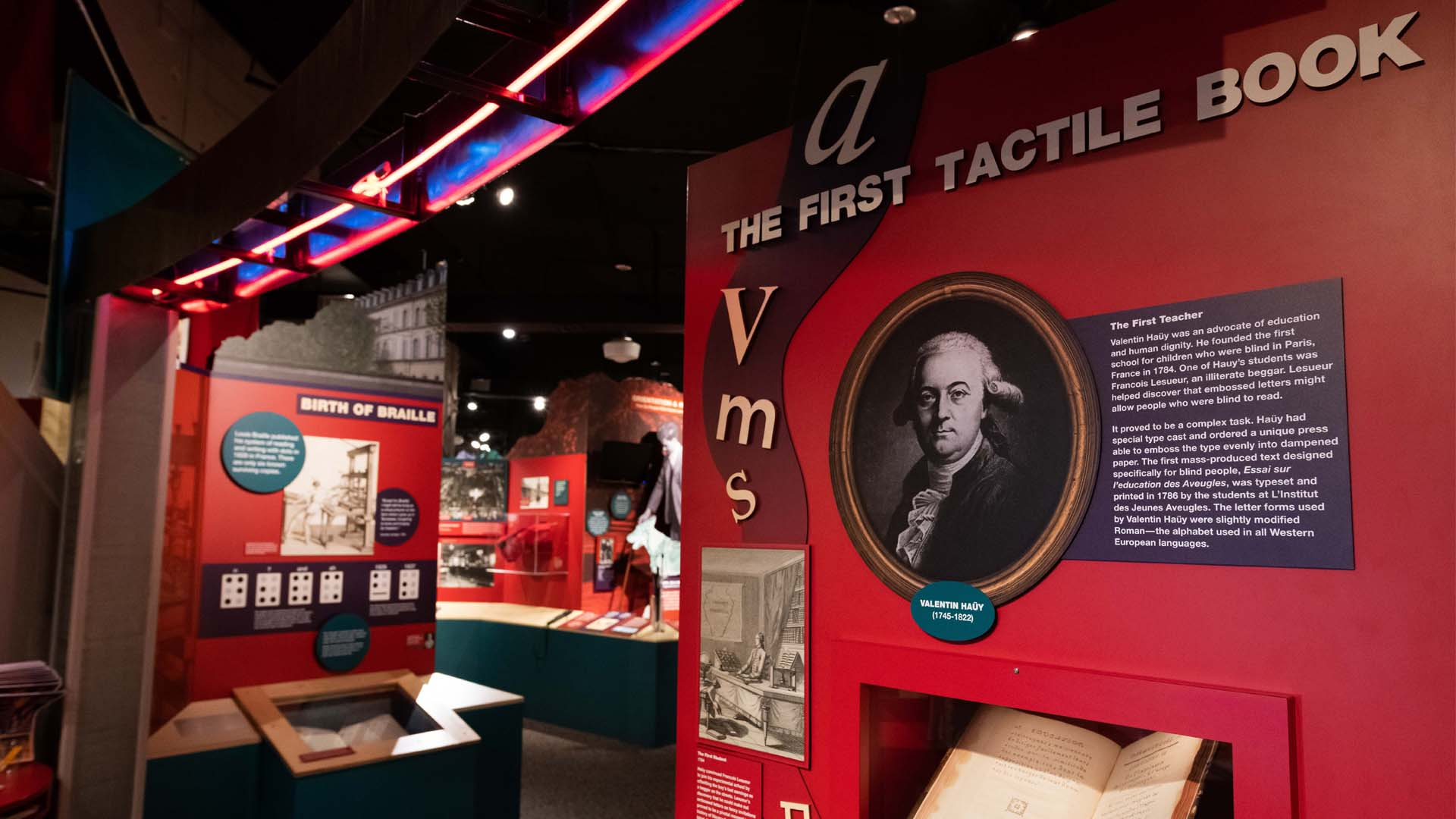 Angled view of museum exhibits, with a display case in the foreground holding a tactile book