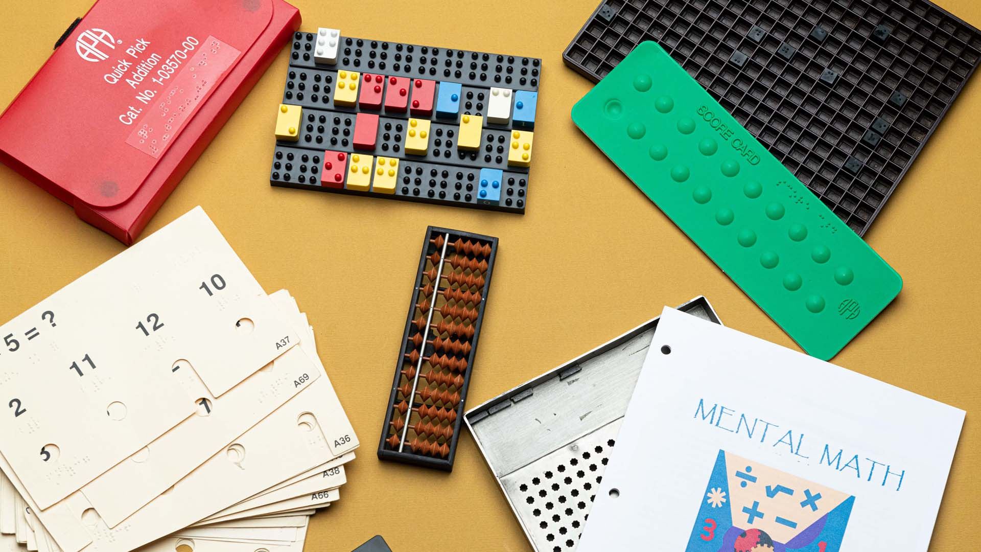 Scattered math tools, including flashcards, an abacus, a cubarithmn slate, and lego blocks with braille symbols on top