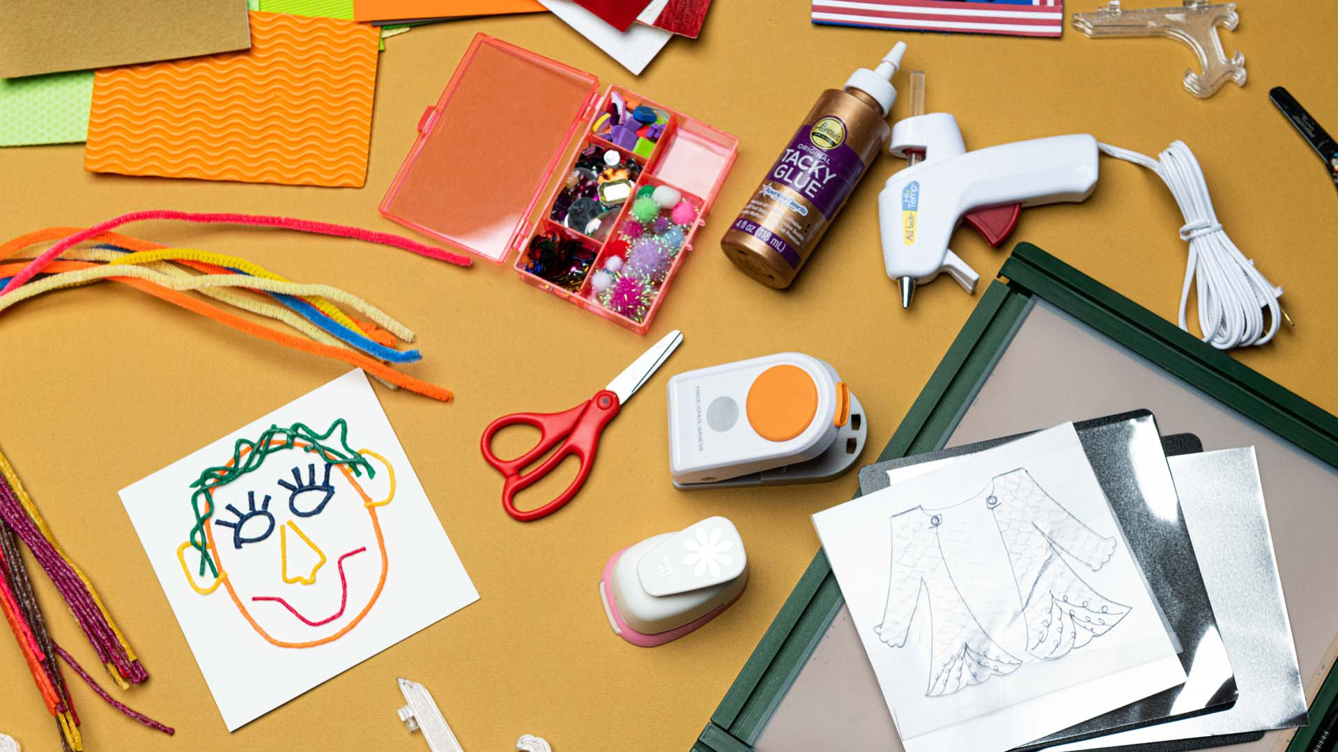 Scattered crafting tools including colorful papers, a bottle of glue. a glue gun, scissors, tactile beads in a tray, embossing foil, and a card with a funny face created with colorful waxed yarn