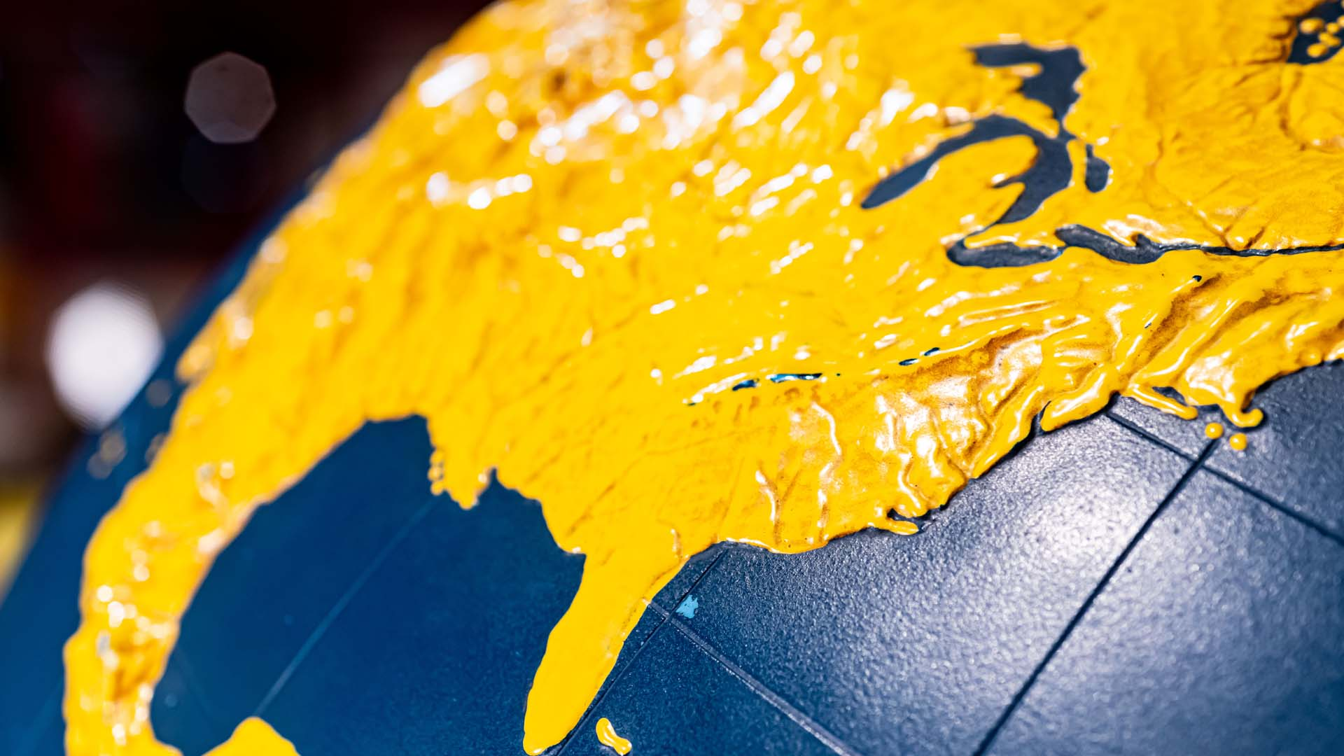 Closeup of a relief globe with the land in yellow and the water in blue