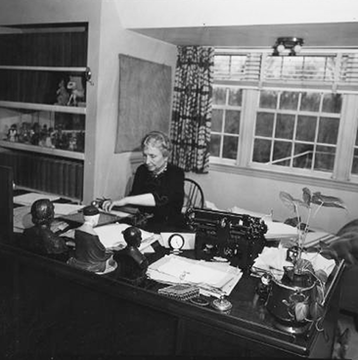 A black-and-white photograph of Helen Keller typing on a braillewriter at a large desk covered with potted plants, stacks of paper, and scattered art objects and paper weights