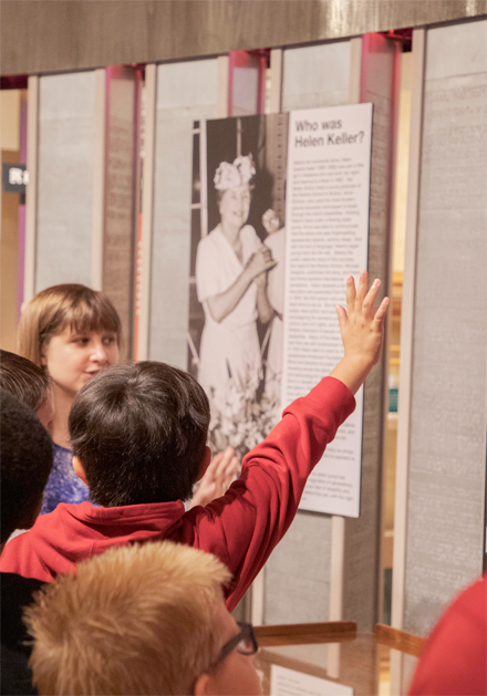 A woman describes a museum exhibit while children crowd in, with one boy raising his hand to get the woman's attention