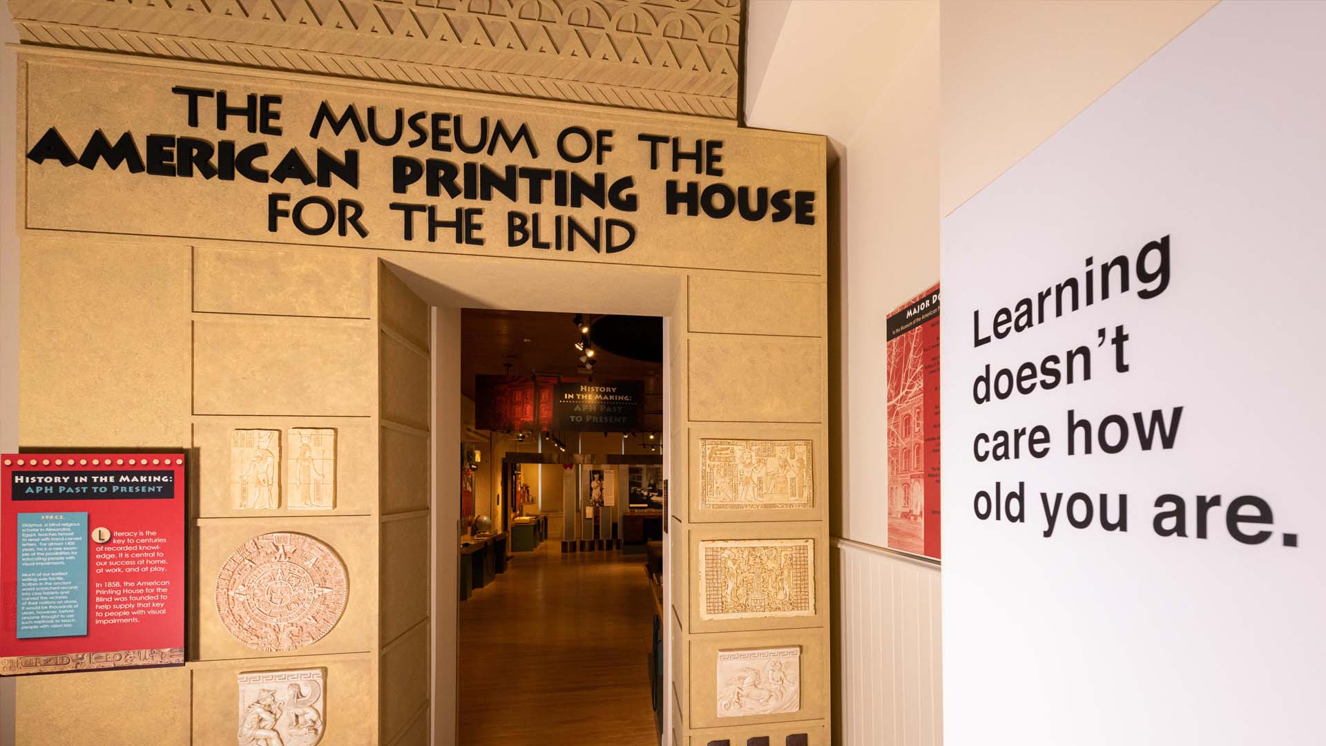 """An entry into a museum exhibit, flanked by mounted examples of early tactile writing. Above the entry in large black letters is """"The Museum of the American Printing House for the Blind."""" Other museum signs are on the margins of the image."""