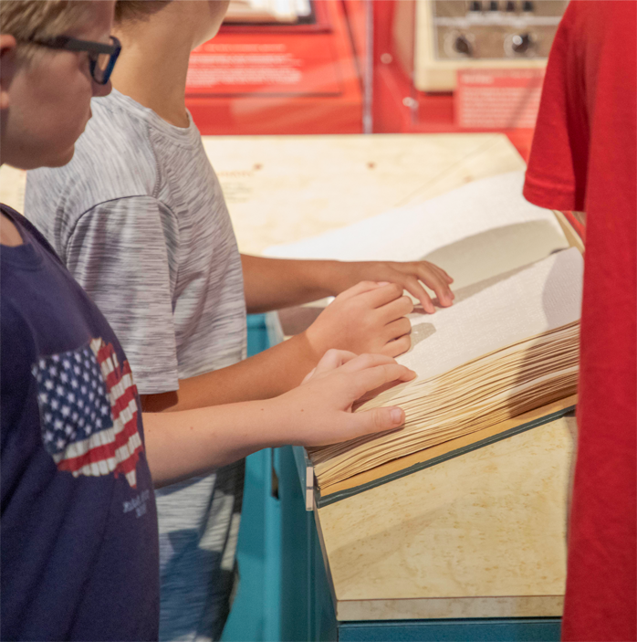 Two boys in t-shirts touch the pages of a large braille encyclopedia