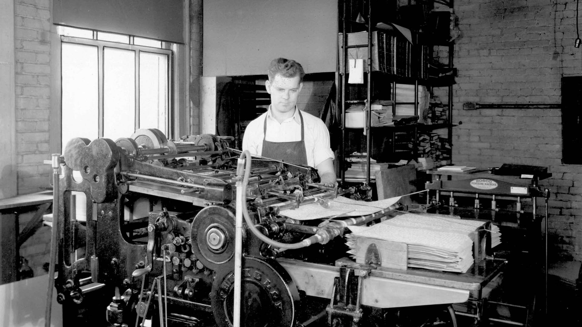 A man wearing an apron stands behind a bulky printing press watching braille pages stack up on the right in a printshop