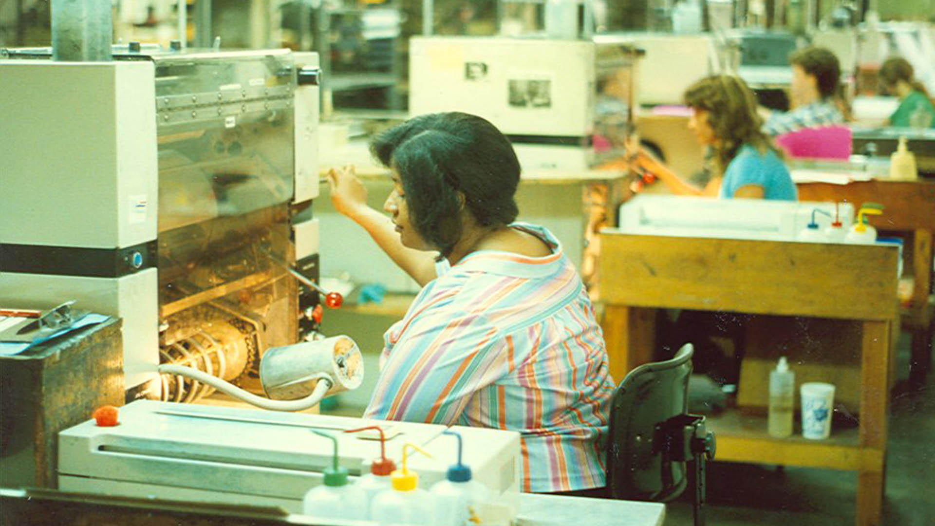 Dark haired woman wearing a colorful striped blouse sits and operates a boxy printing press with a line of other machines and operators stretching off to right in the background