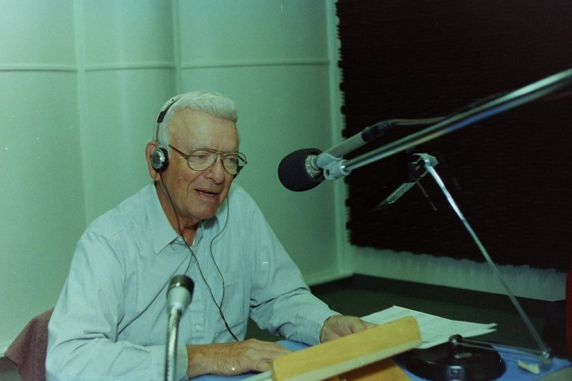 Randy Atcher, a man with short white hair, wearing a white longsleeve shirt, sitting in a recording booth in front of a boom microphone with his hands on a book on a reading stand