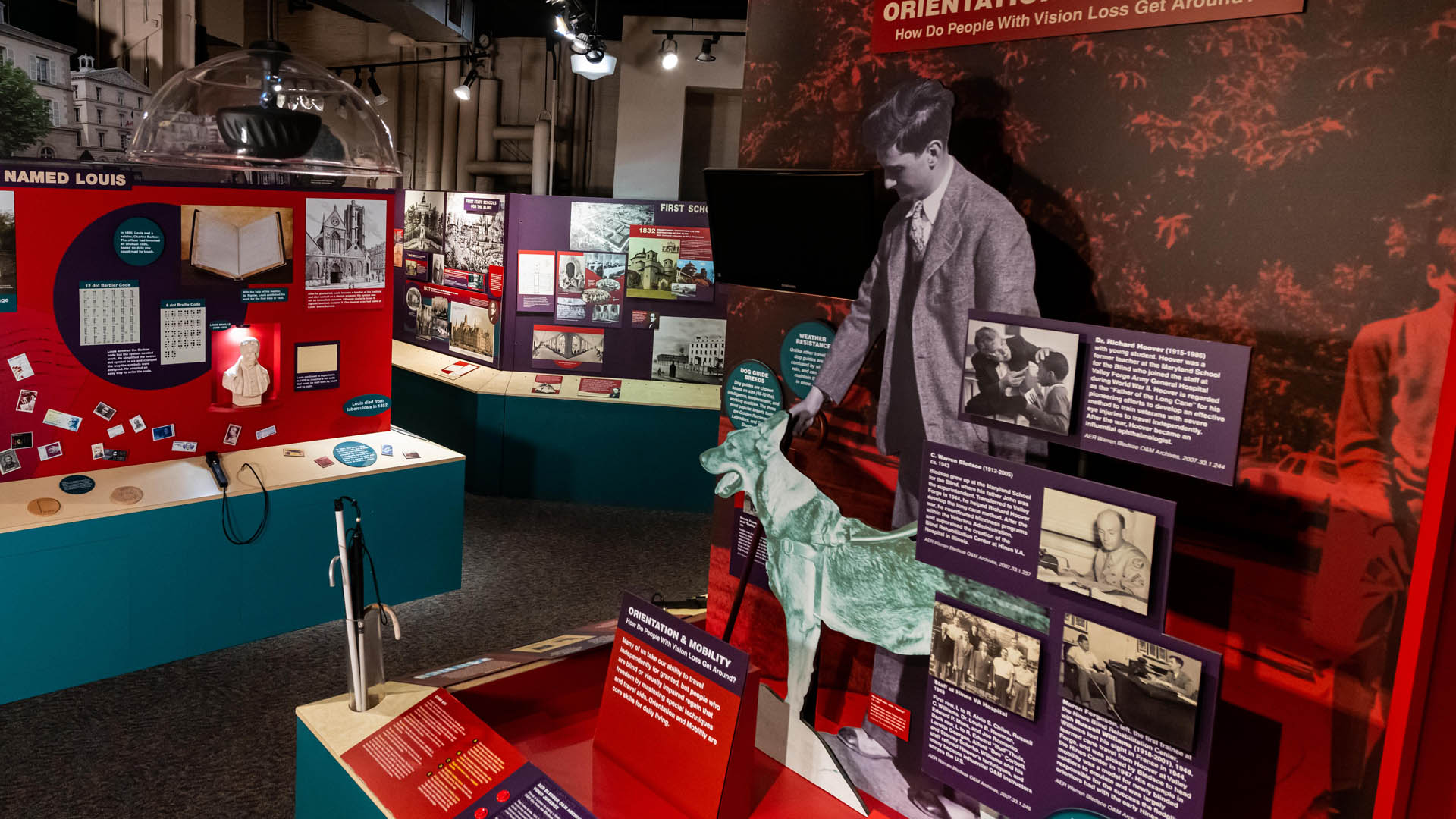 Wide angle photo of museum exhibits with elements on Louis Braille, dog guides, and early schools