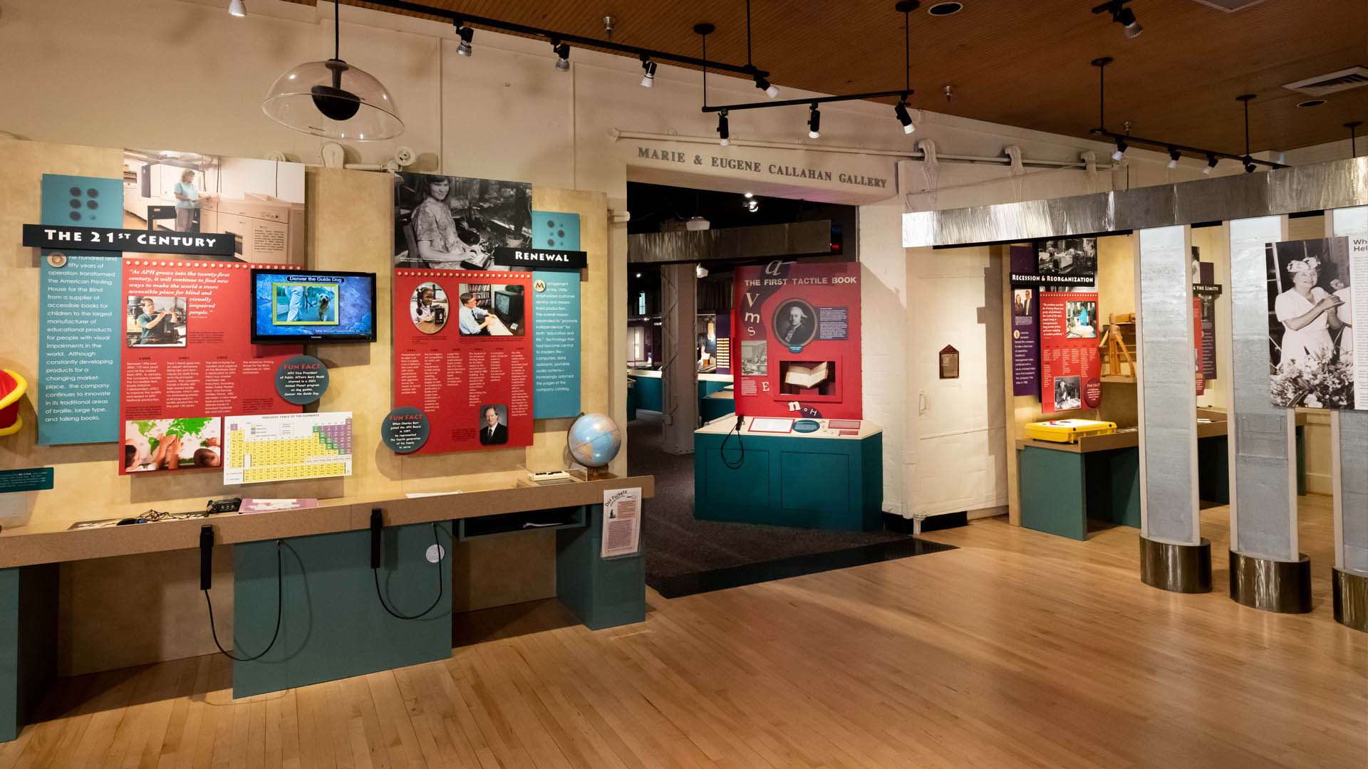 """Wide angle view of a museum exhibit with exhibit panels and display cases to left and entrance on right titled """"Marie and Eugene Callahan Gallery"""""""