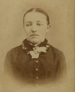 Portrait of Mary Ingalls, her hair pulled back, wearing a dark dress with large buttons down the front and a decorative ruffled collar. She looks slightly down and is not smiling.