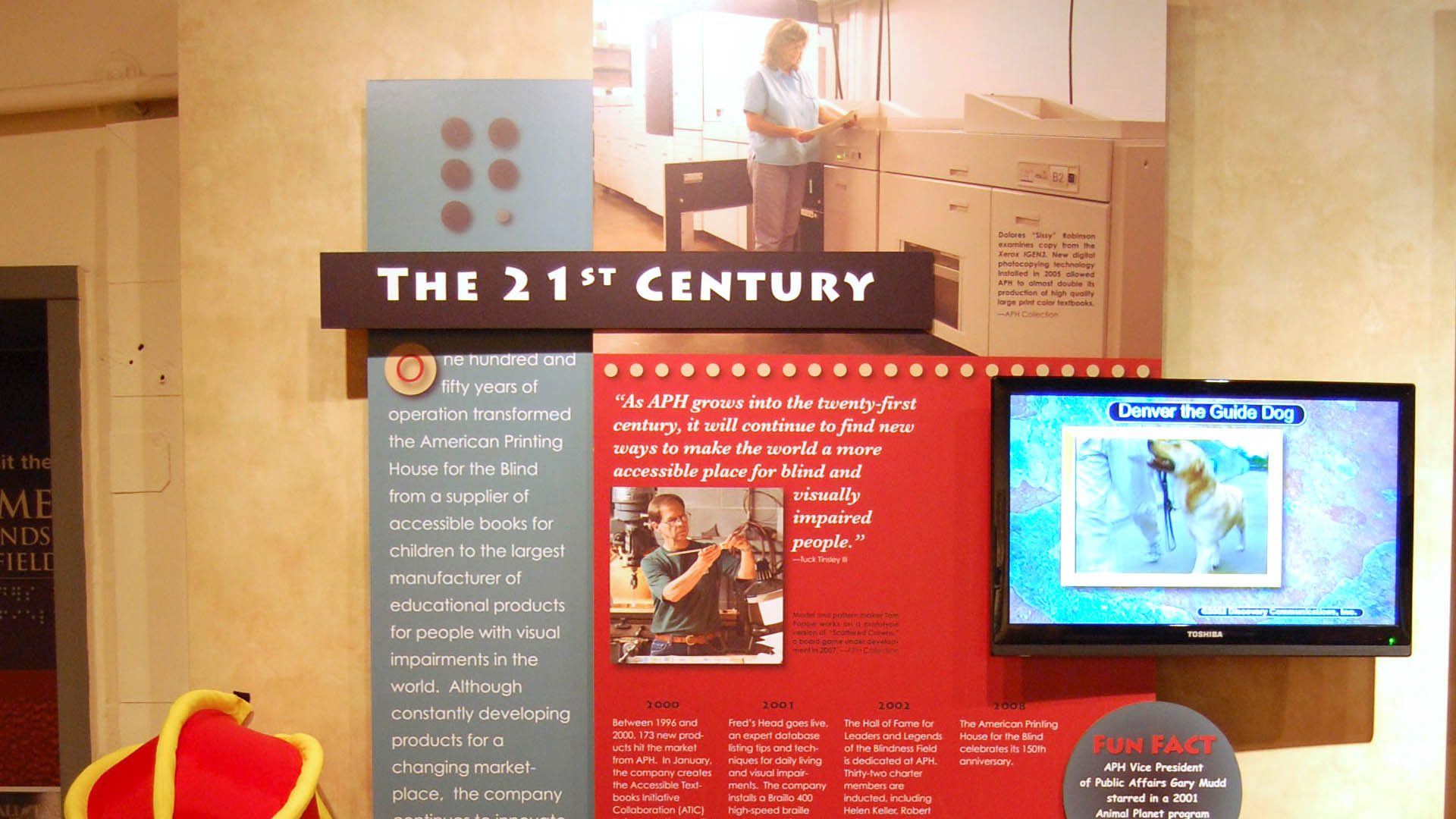Closeup of a museum exhibit panel with photographs of APH workers, large type text, and a monitor showing a video about a dog guide