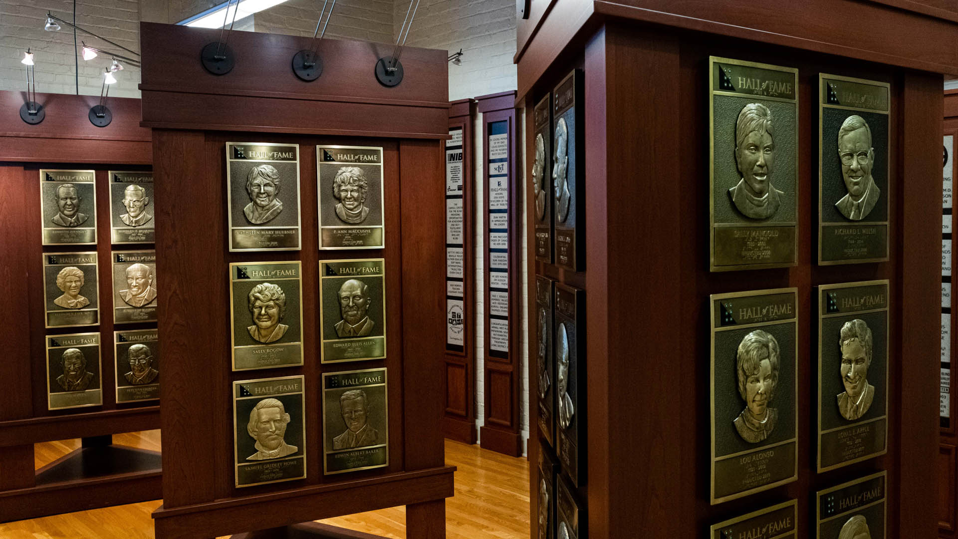 Triangular wooden stands in the Hall of Fame feature gold tone plaques with relief sculptures of people's faces