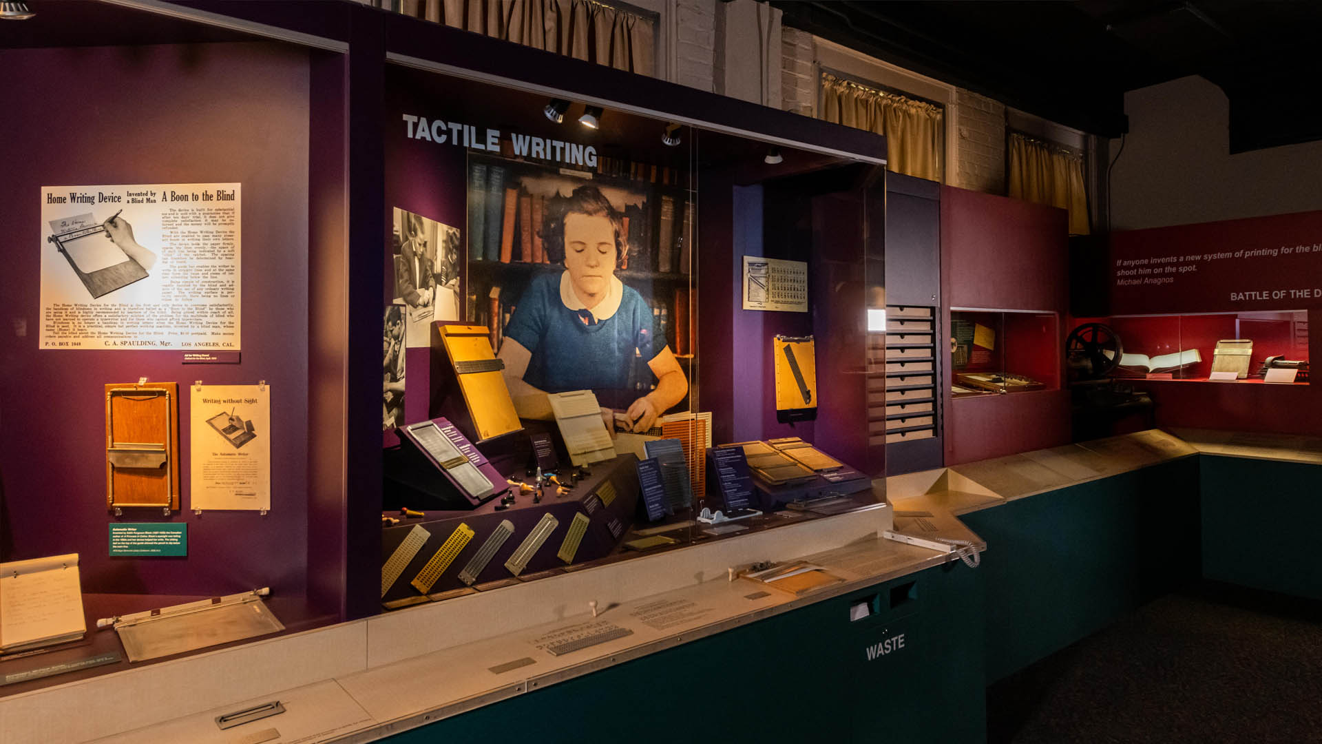 A museum exhibit featuring a case full of braille slates, a picture of a girl writing braille, and a reading rail with tools mounted to it