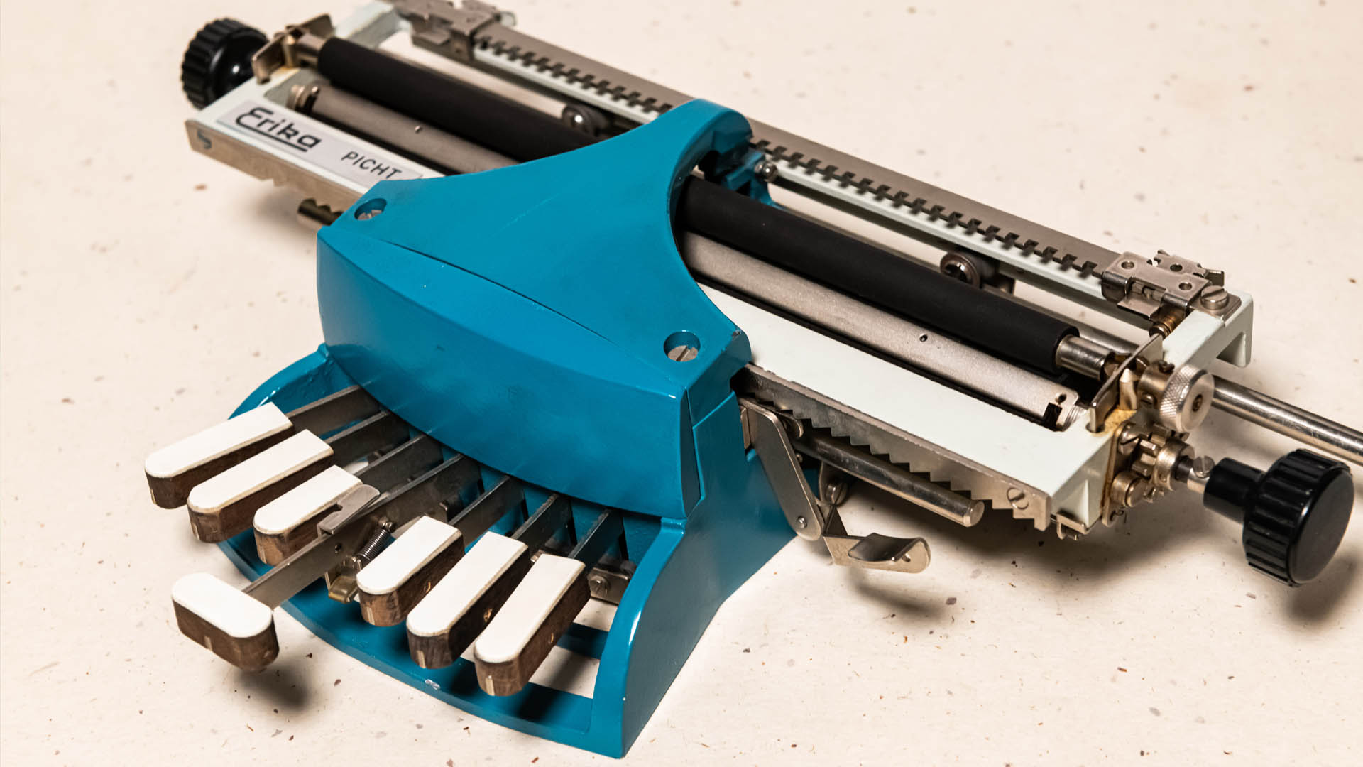 Braillewriter with a blue metal frame, a bright metal paper carriage , and seven wooden keys topped with white plastic keypads
