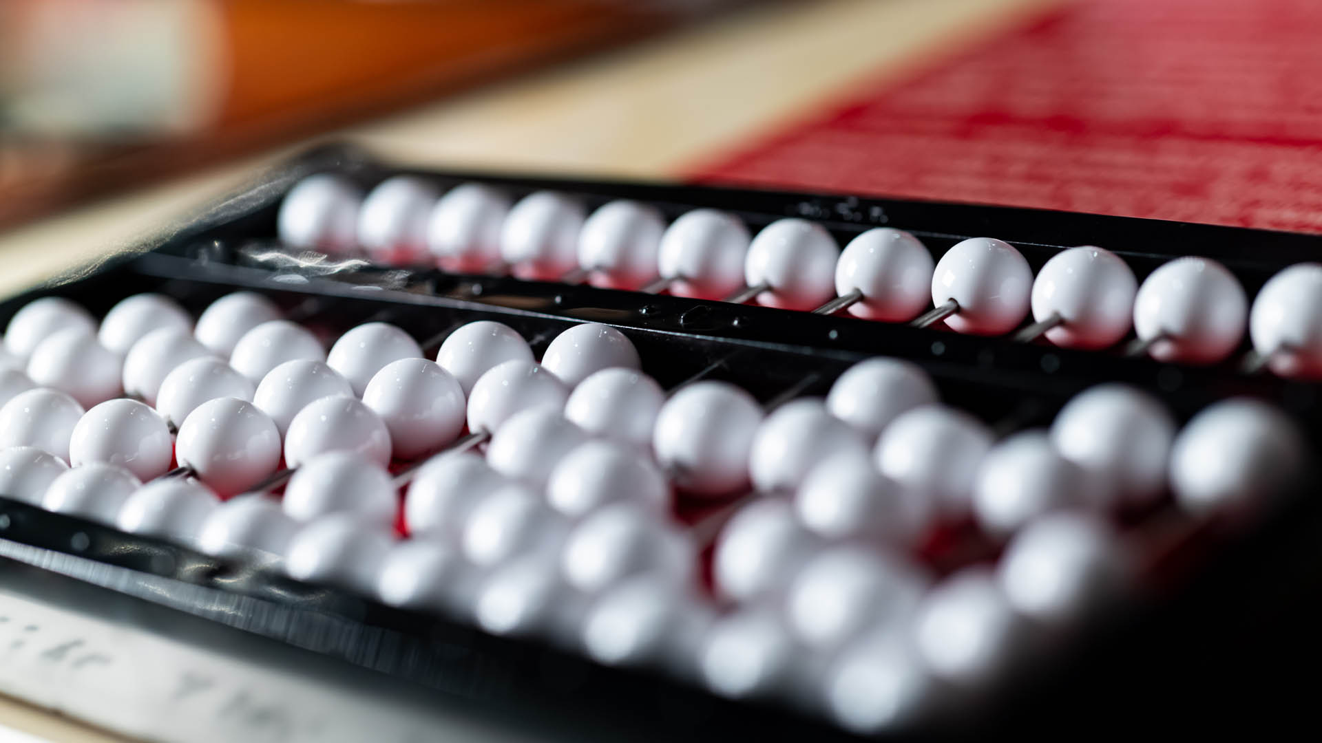 Closeup view of white plastic beads on an abacus