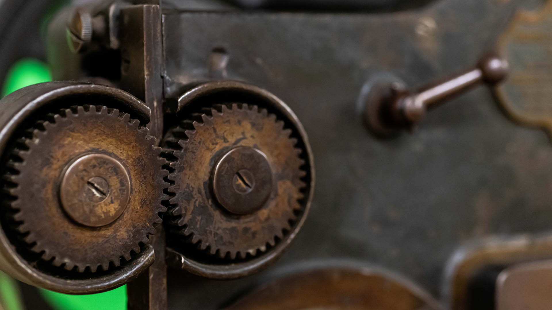 Detail of two metal gears on the side of a wire stitching machine