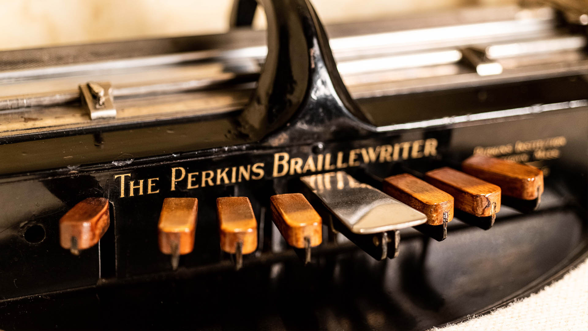 """Closeup of keyboard on black braillewriter with stenciled gold lettering above keys reading """"The Perkins Braillewriter"""""""