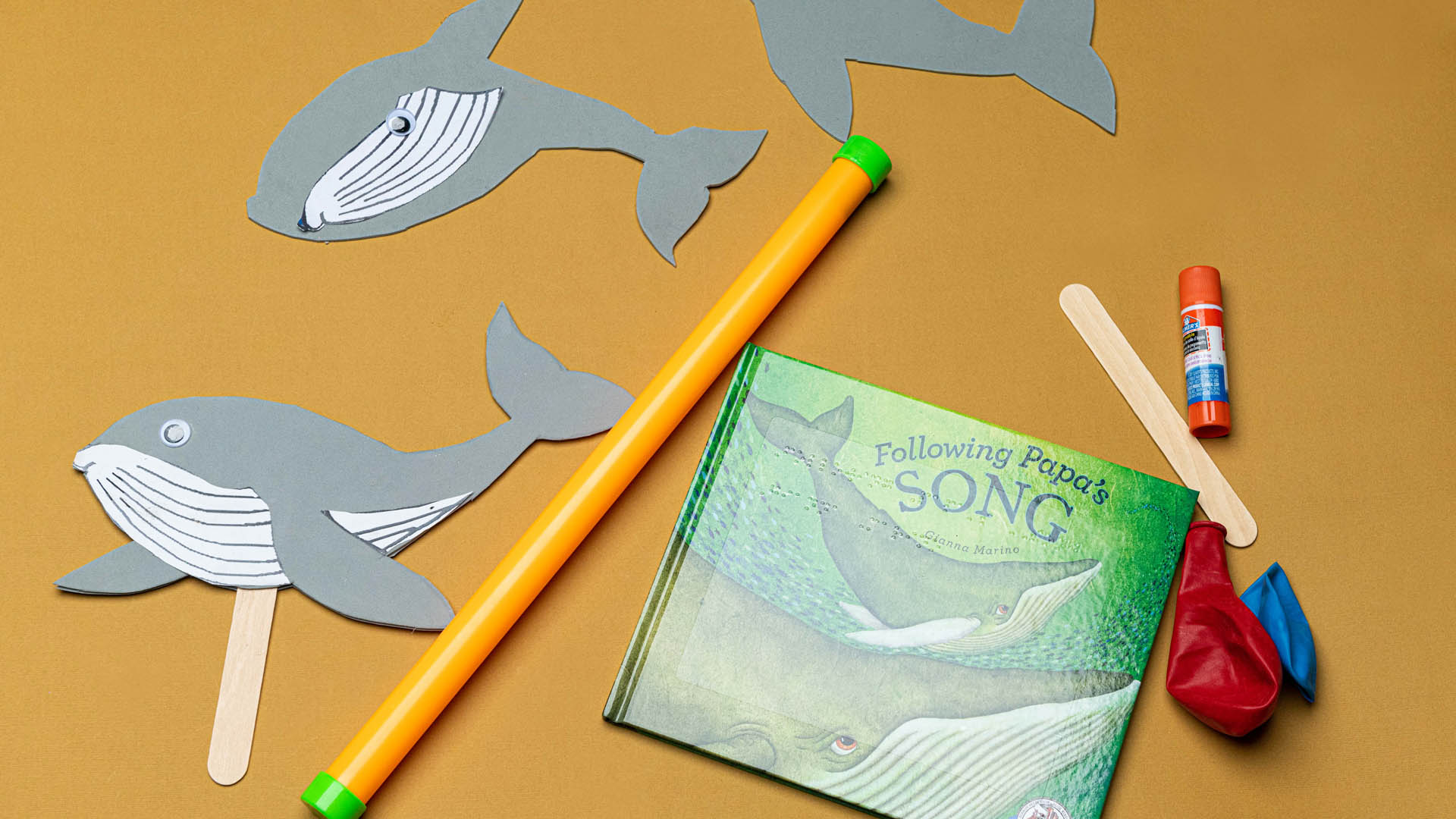 """Book titled """"Following Papa's Song"""" and craft materials to create a whale puppet"""