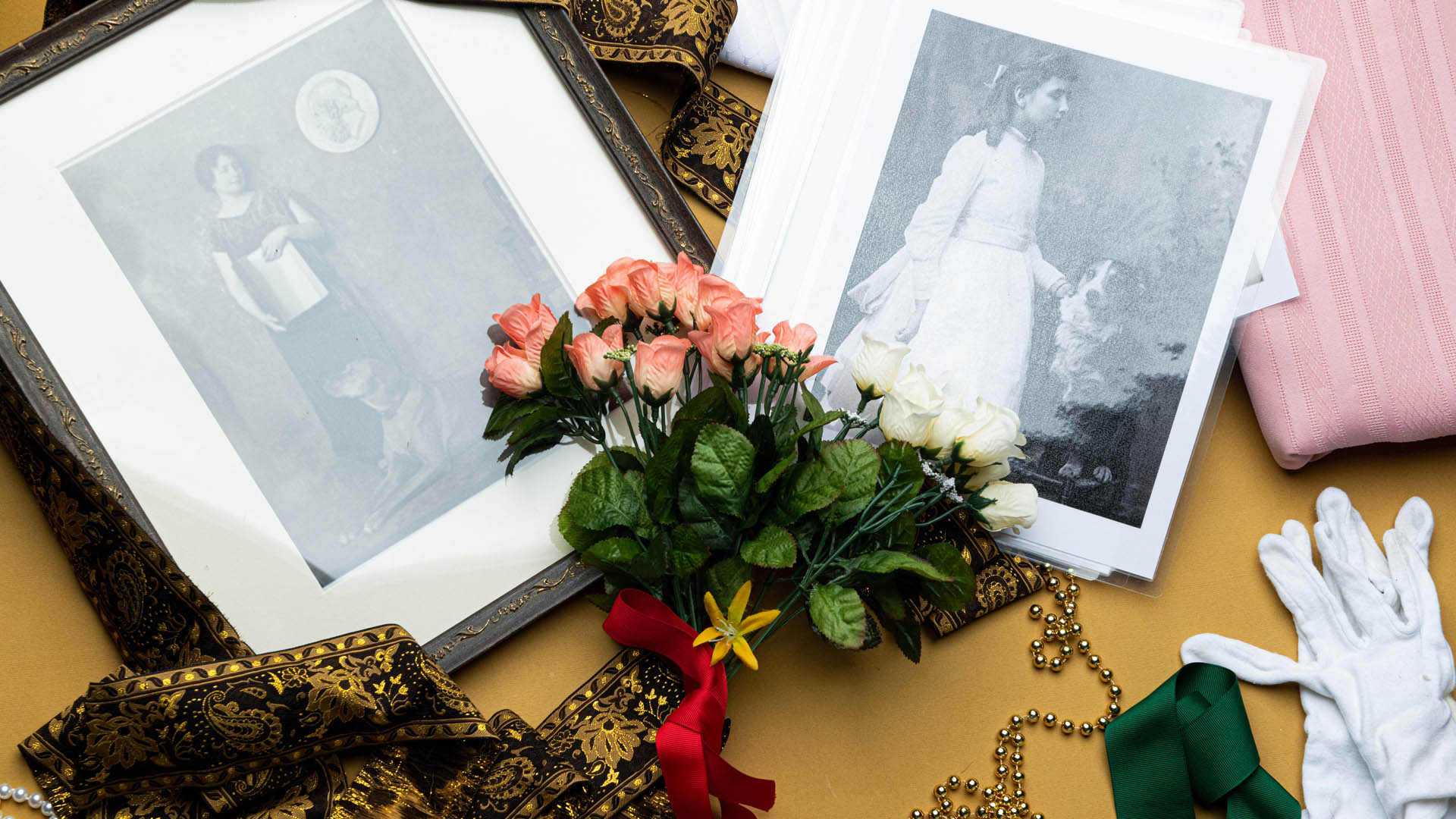 Scattered items including photographs of Helen Keller as a child and adult, white gloves, a spray of flowers, beads, and colored fabrics