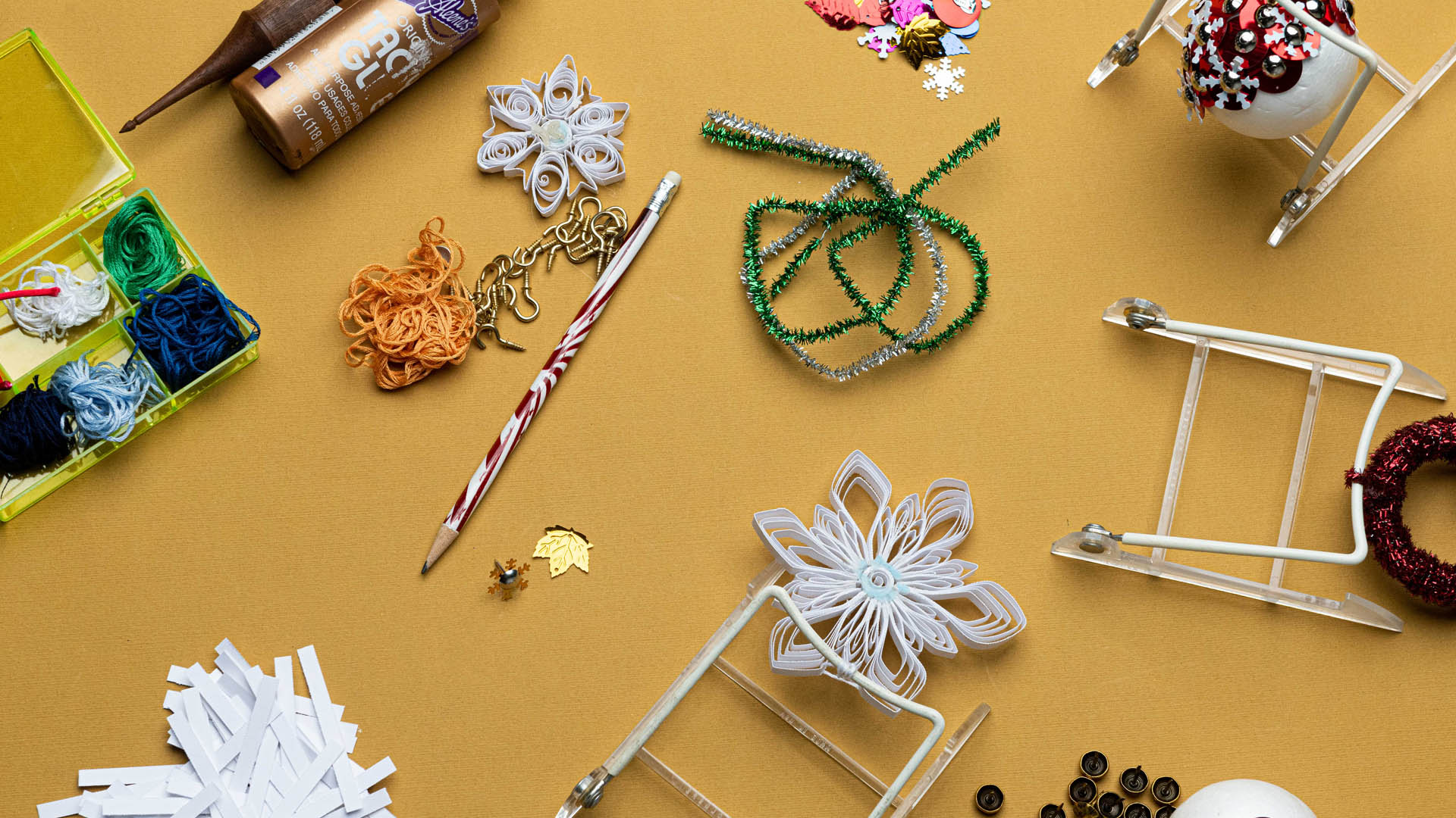 Detail of craft supplies laid out on a gold background