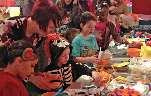 Children and adults making Halloween masks