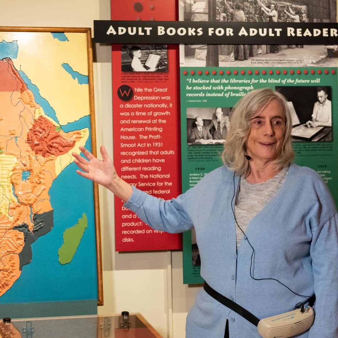 Tour guide in a blue sweater wearing a headset microphone gestures towards a colorful tactile map of Africa